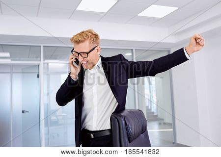 The concept of success, victory, business. Businessman blonde with glasses raised his fist up, talking on phone smiling, laughing.