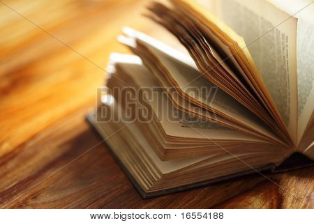 Book or bible on a wooden desk in a library or classroom