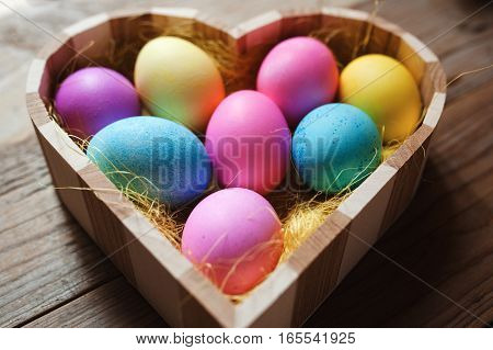 Easter symbol - heart shaped wooden bowl full of colored eggs