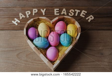 Happy Easter - colored eggs in a heart shaped bowl on a wooden background