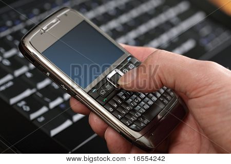 Using a PDA mobile phone with laptop keyboard background, blank screen for copy