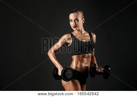 Side view of sexual muscular blonde with ponytail in bikini posing with dumbbells on black background.