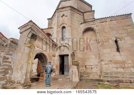 Man praying at entrance of the Jvari Monastery built in 6th century in Mtskheta, Georgia. World Heritage site by UNESCO
