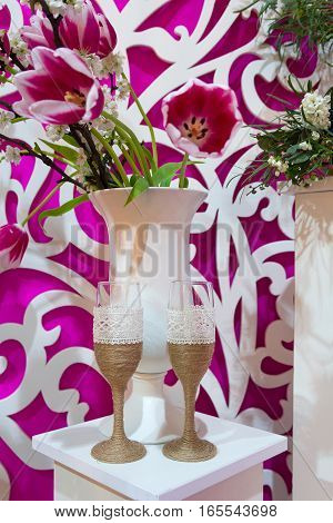 Decorated glasses and a bouquet on a table at a wedding ceremony