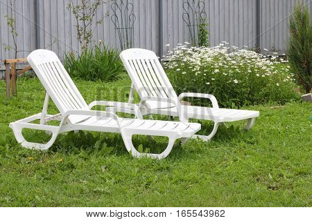 Two white sun loungers for sunbathing in the suburban area garden
