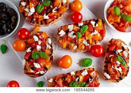 Tasty Traditional Tomato bruschetta with feta cheese topping, fresh basil and balsamic vinegar.