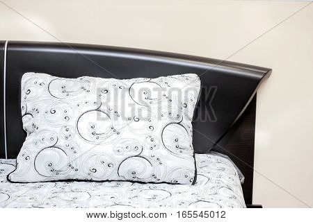 White pillow with black embroidered patterns on a powerful bed of ebony