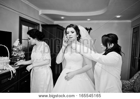 Bridesmaids Helping Dressed Bride On Wedding Day At Morning. Black And White Photo