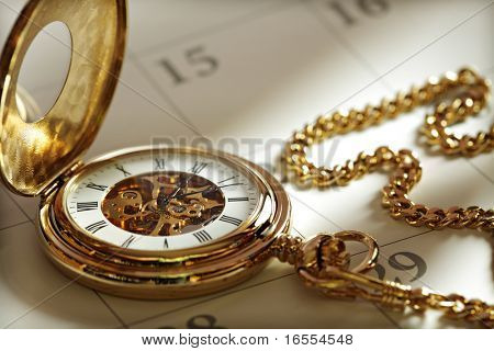 Close up di un orologio da tasca d'oro su un calendario alla luce del sole