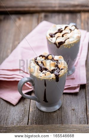 S'mores drink. Two mugs of hot chocolate with marshmallows on a wooden table. Cocoa drink.
