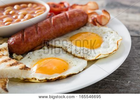 Traditional full English breakfast with fried eggs, sausages, beans, mushrooms, grilled tomatoes and bacon on wooden background