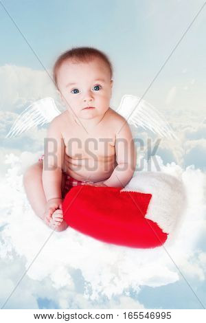 Baby Newborn with Angel Wings and soft pillow. Child Sitting at Blue Sky Cloud. Artistic Fantasy Sky Background.