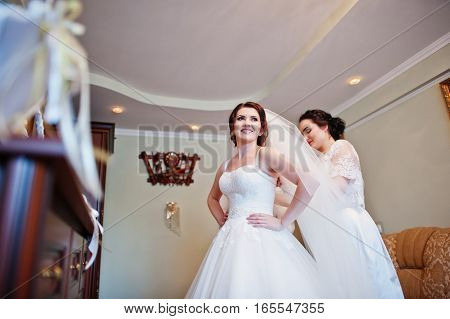Bridesmaids Helping Dressed Bride On Wedding Day At Morning.