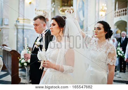 Bridesmaid holding wedding crown at had of bride on church.