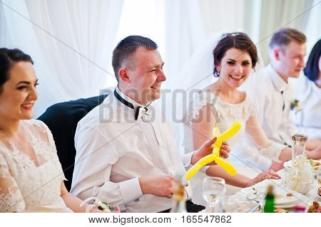 Wedding Couple With Bridesmaids And Best Man Sitting At Table On Restaurant.
