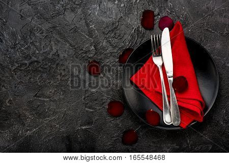 Fork, knife with red napkin, roses and black plate. On dark table background.