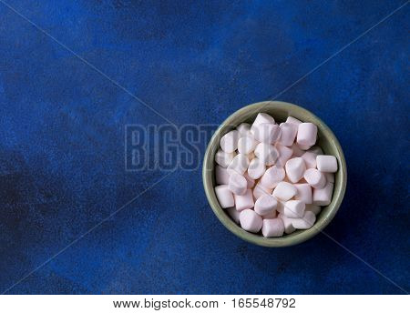 Marshmallows in plate and on blue background. Toned image with copy space for text. Top view.