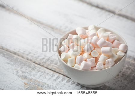 Marshmallows in plate on white rustic wooden background. Toned image with copy space for text