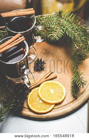 Hot tea with cinnamon on a wooden board with branches of spruce