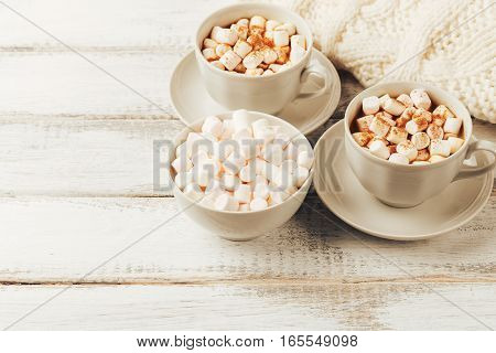 Cups with hot coffee or cocoa and marshmallows, white knitted blanked on white rustic wood table. Cozy winter. Toned image. Copy space