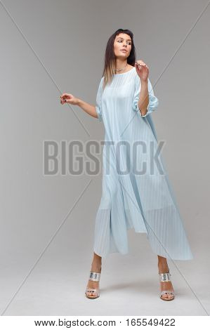 Serious confident woman posing in light blue dress and holds it with one hand