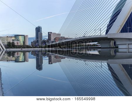 Valencia, Spain - December 20, 2016: old dry riverbed of the River Turia, Gigapan reflection in the water of a bridge, Office buildings and shopping. Europe