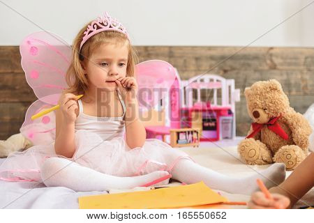 What do I want to draw. Little thoughtful girl touching her lips while sitting in a room. Child looks like a pretty fairy with pink wings