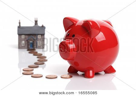 Real estate or home savings - red piggy bank, coins and a house