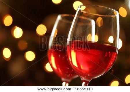 Wineglass with red illuminated defocussed christmas light background