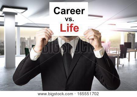 businessman in modern office hiding behind sign career versus life