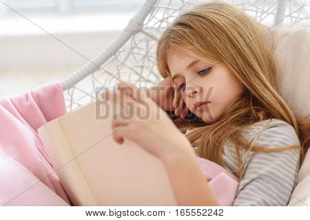 Pensive female child is reading book with interest. She is lying on hammock and relaxing