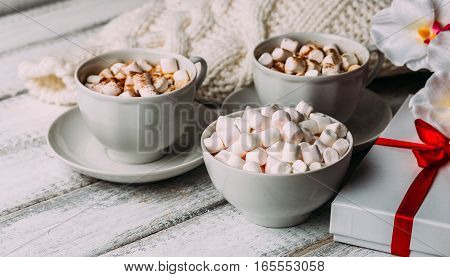 Cups with hot coffee or cocoa and marshmallows, gift box with red ribbon, white knitted blanked and flowers on white rustic wood table. Valentines day concept. Cozy winter. Toned image.