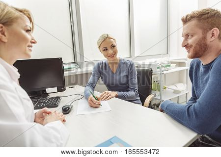 Happy smiling couple is sitting afore kind doctor. She looking at patients with smile