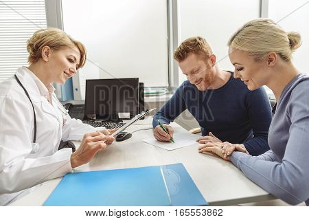 Happy couple is sitting afore benevolent doctor. Man writing carefully. Medical advisor attentively looking though information on clipboard