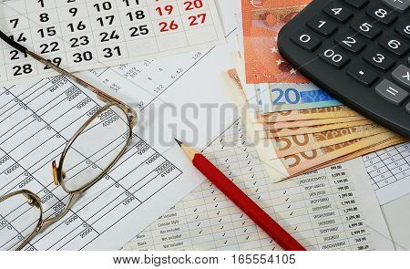 Papers with figures calendar glasses red pencil euros and calculator placed on a table