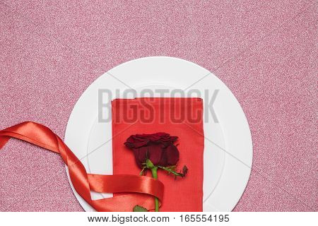 red rose with ribbon on plate on red background. Valentine's day.