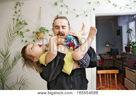 dad and daughter playing together, happy family authentic portrait at home