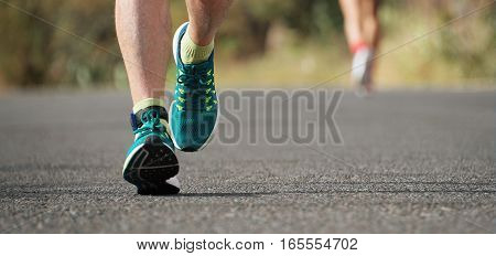 Runner man running on road training for marathon run doing high intensity interval training sprint