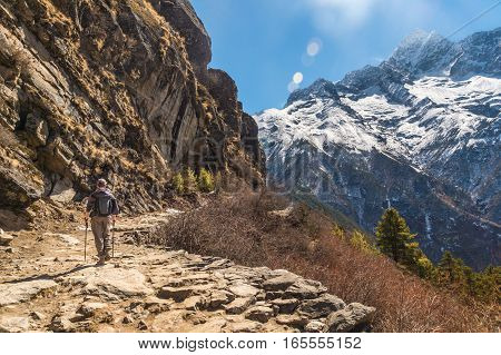 Trekker on a trail in the Himalayan region with mountain range in the background