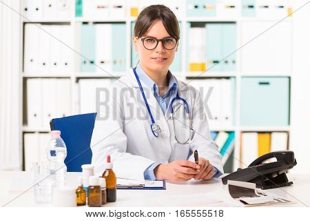 Pretty young smiling female doctor with stethoscope around neck sat at desk
