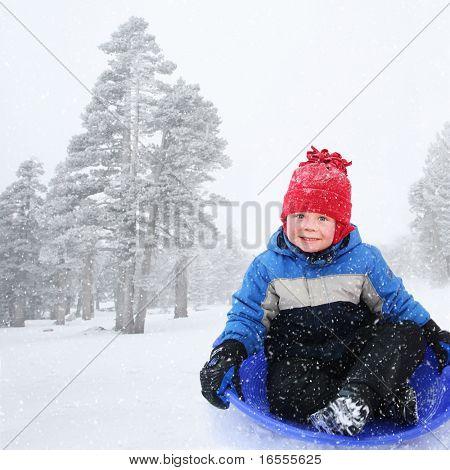 Four year old boy sledding in snowy landscape