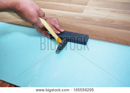 Man Installing New Laminate Wood Flooring. Worker Installing wooden laminate flooring. Step by Step.