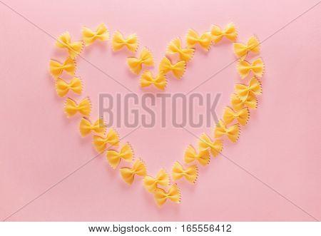 Heart frame from wheat pasta farfalle on rose background. Random pattern. Flat lay.
