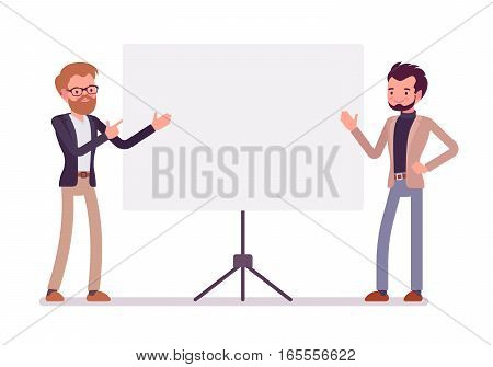 Young handsome successfull businessmen near the standing presentation display board, pointing with hands, talking about startup, demonstration of managment ideas, full length, copy space
