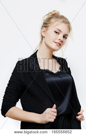 beautiful young blond woman in a black dress posing on a white background