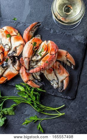Seafood. Crabs tentacles on black plate with wite wine, lemon and herbs sauce on slate background. Top view