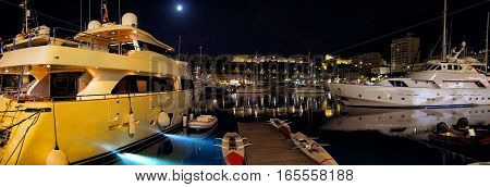 luxury yachts or sailboats at moorage in sea port pier at night under moon light on dark sky background