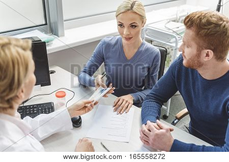 Gynecologist is sitting afore couple. She giving few empty tubes to female patient. Man looking at wife