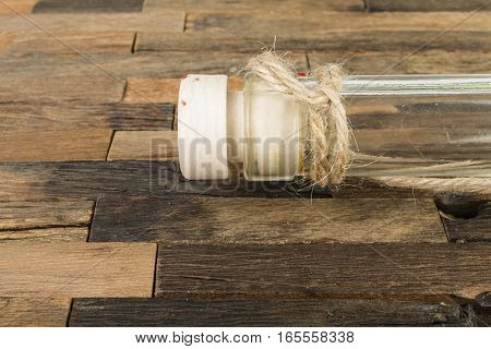 Bottle with cork on wooden background. Macro shot.