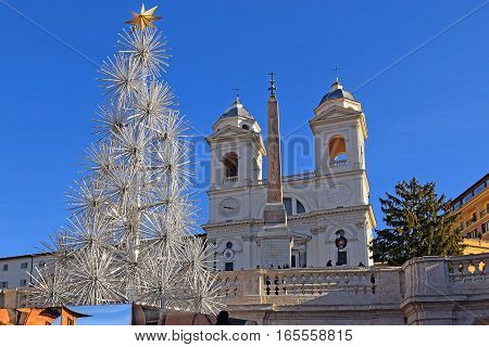 unusual Christmas tree, obelisk and church Trinita dei Monti on top of the Spanish steps, Rome, Italy